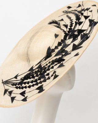 Pamela de sinamay adornada con plumas tipo flecha a contraste.