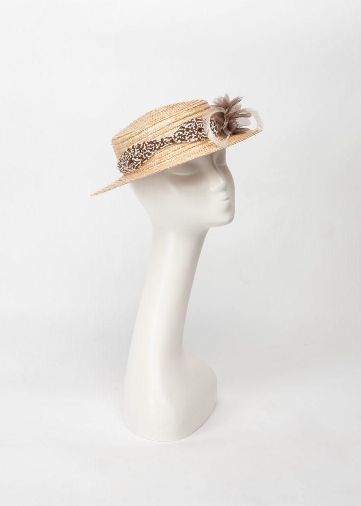 Canotier de paja trenzada adornado con una pieza bordada a mano, plumas de oca biot y flor de organza con pistilos.