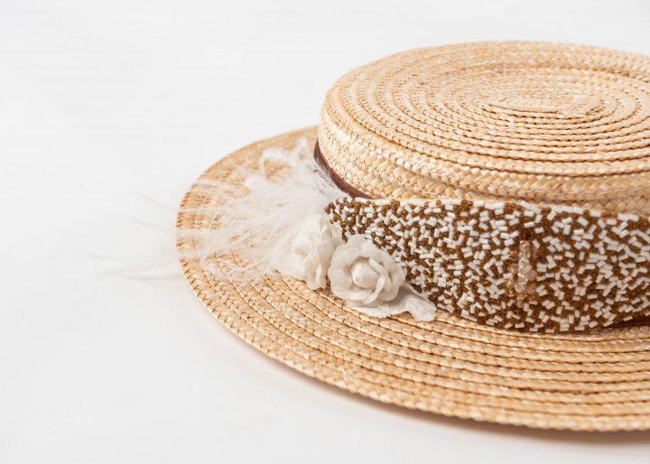 Canotier de paja trenzada con pieza bordada, flores, plumas y cinta.