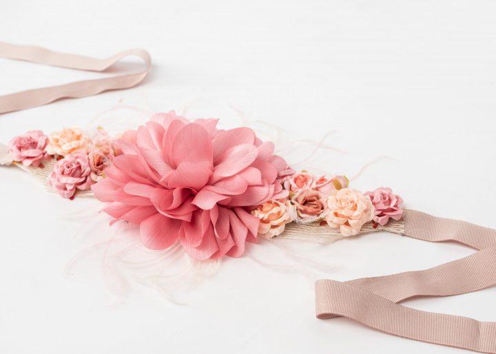 Tocado sobre una base de yute adornao con flores de diferentes tamaños y plumas de avestruz
